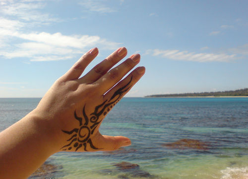 tattoo on hand in front of sea